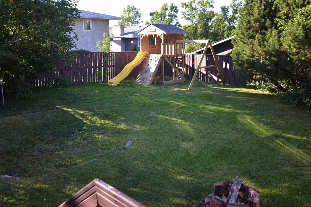 The large, private yard has plenty of grassy area and trees.