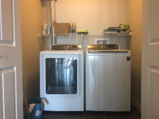 House-sized, side by side laundry equipment & space for additional storage shelving too!
