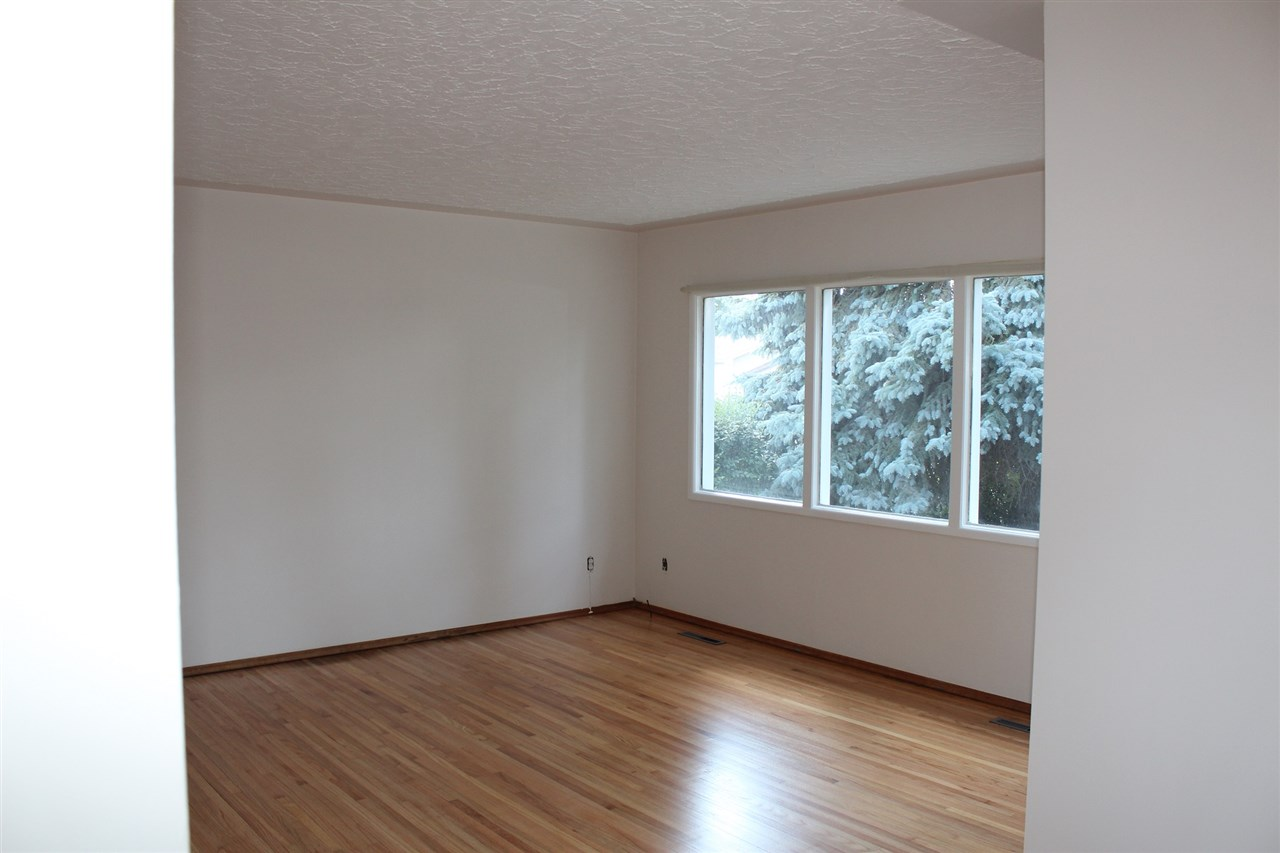 A large living room area with newly refinished original hardwood floors.