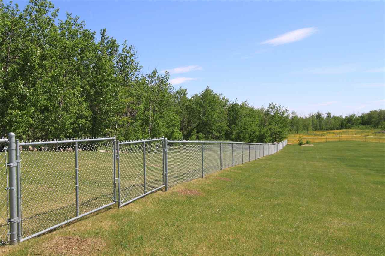 The trees behind the fence is part of the acreage this fully fenced yard is to keep the deer out.