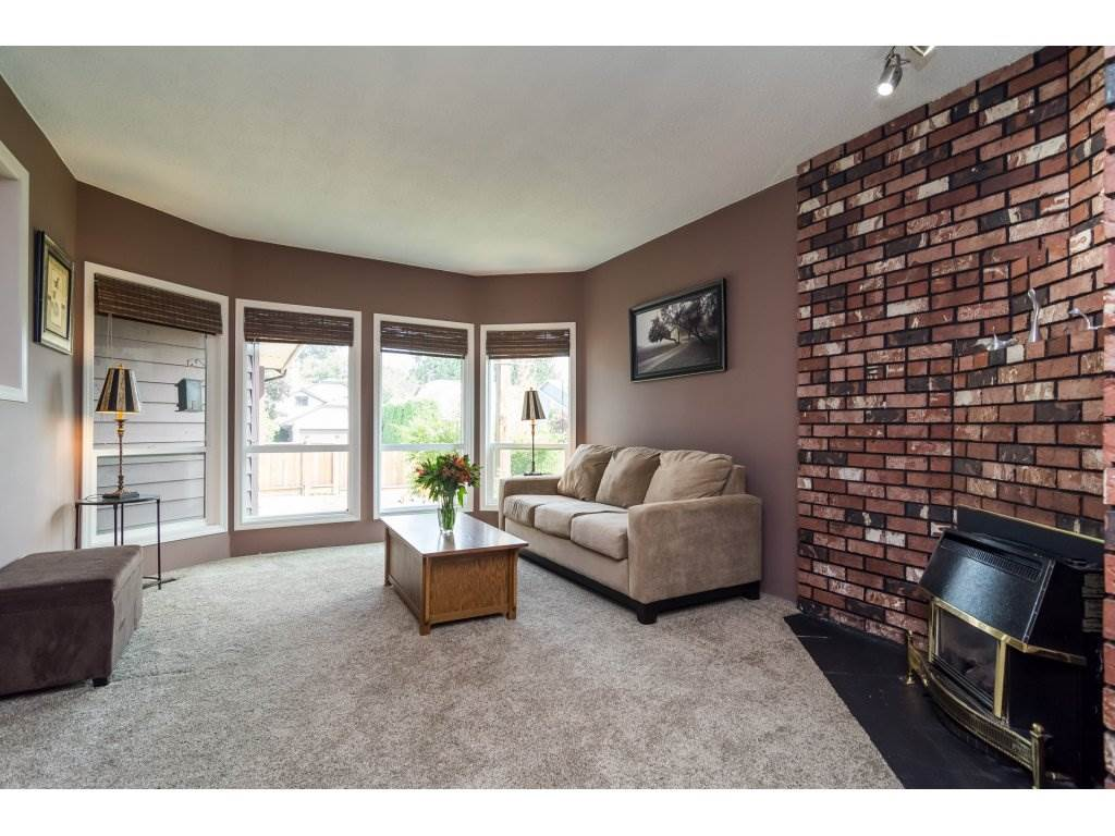 New carpets, large windows and brick  fireplace make this sunken living room a great place to gather.
