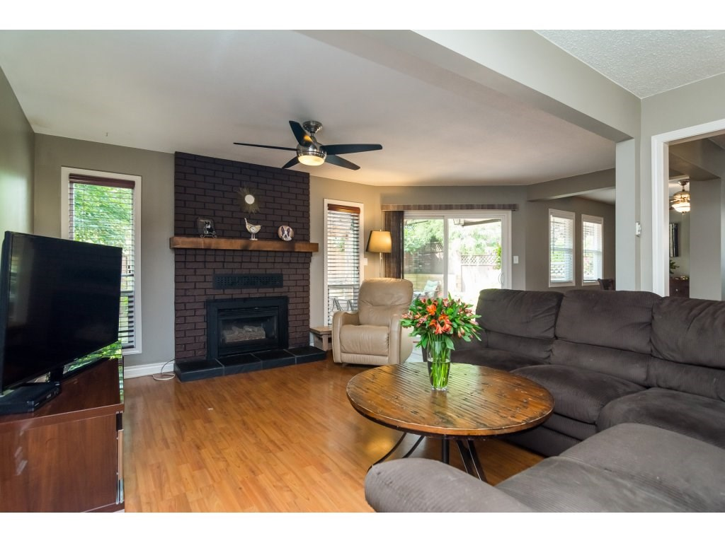 Large family room with fireplace and sliding doors leading to large deck outside.