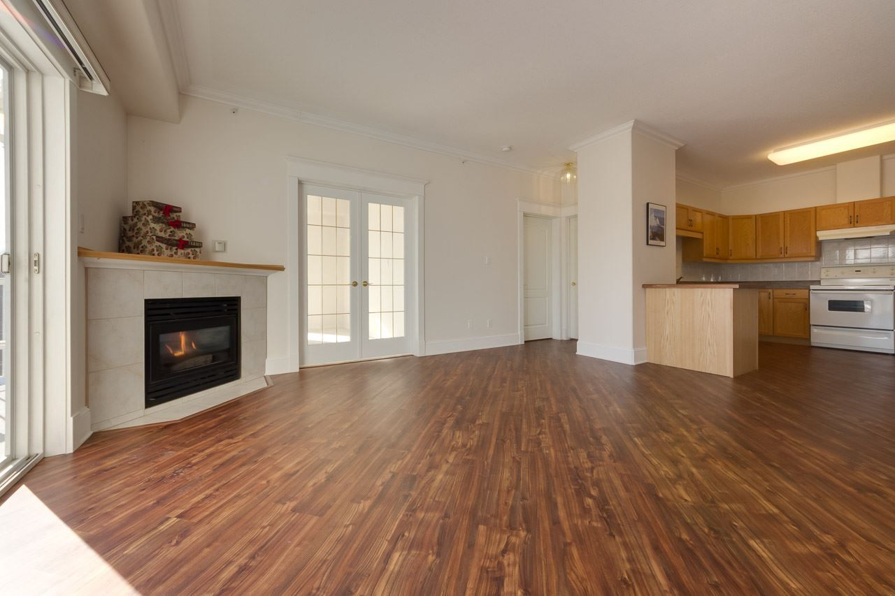 open concept living room features 9 ft ceilings, corner fireplace and is open to the kitchen