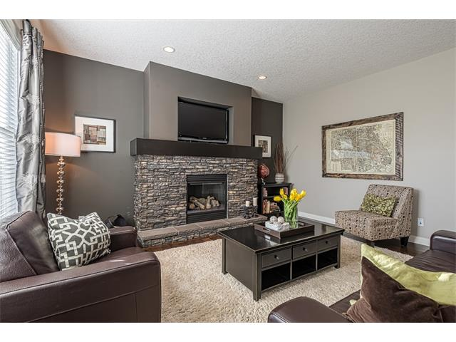 Great room with modern designer colors and stone trimmed gas fireplace.
