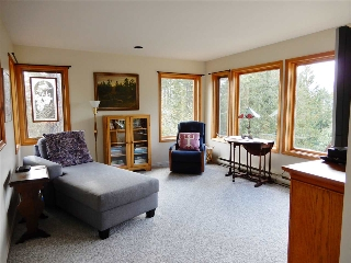 Large living room with lovely large picture windows with wood returns.