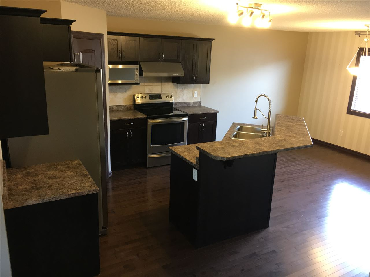 Generous Size Kitchen is open to the Large Dinette Area and Conveniently located next to the 2 Pce Powder Room and Back Entrance. Note the Gleaming Hardwood Floors, Feature Striped Wall, Windows with Custom Blinds & Contemporary Ceiling Light Fixture.