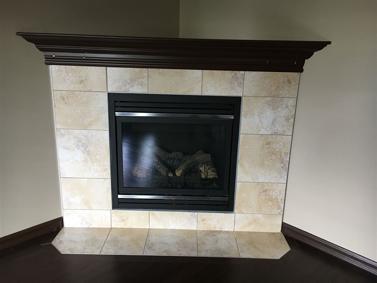 Close up of the Corner Gas Fireplace in the Living Room showing the Ceramic Tile Surround and Wood Mantle.