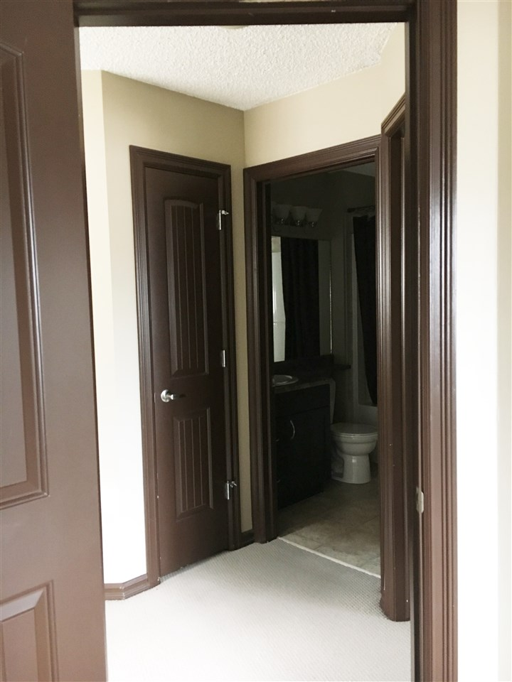 The Upper Hall as Seen from the 3rd Bedroom Showing the Linen Closet Door to the Left and the Shared 4 Piece Bathroom at the Rear. The 2nd Bedroom is to the Right of the Bathroom. Note the Attractive Dark Wood Doors & Trim and the Neutral Carpet & Walls.