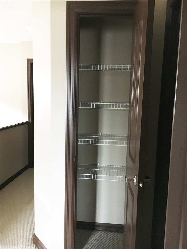 The Upper Level Linen Closet with Metal Shelving is located in the Hall Near the Bathrooms and 2nd/3rd Bedrooms.