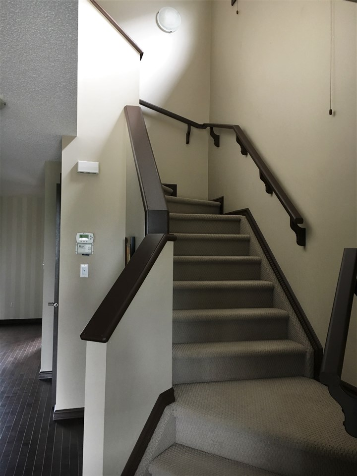 Staircase to the 2nd Level from the Foyer Showing the Carpeted Stairs; Dark Wood Railings & Along the Side showing Thermostats, Knob of Door to Lower Staircase, Past the Kitchen to the Striped Accent Wall of the Dinette Area & Back Entrance on  the Right