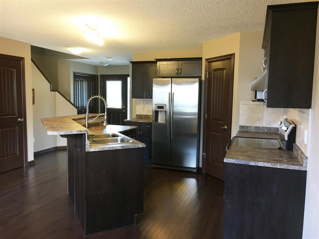 Photo of Kitchen showing Centre Island,Dble Sinks/Uupgraded Tap;SS Fridge(Water/Ice Dispenser),Front Entrance,Staircase,Door to Lower Level as Viewed from the Dining Area.Note the Gleaming Hardwood Floors/Cabinets & Open Floor Plan.Such aDelightful Home!