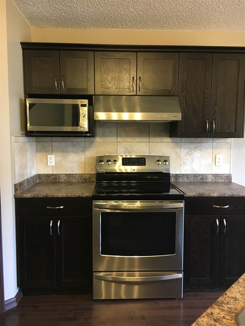 Kitchen Photo Showing Beautiful Dark Wood Cabinets;the Stainless Steel Stove/Ceramic Top,Hood Fan & Microwave. Note the Attractive Ceramic Backsplash & Arborite Counter Tops. BI Dishwasher & Fridge (water/ice Dispenser not shown