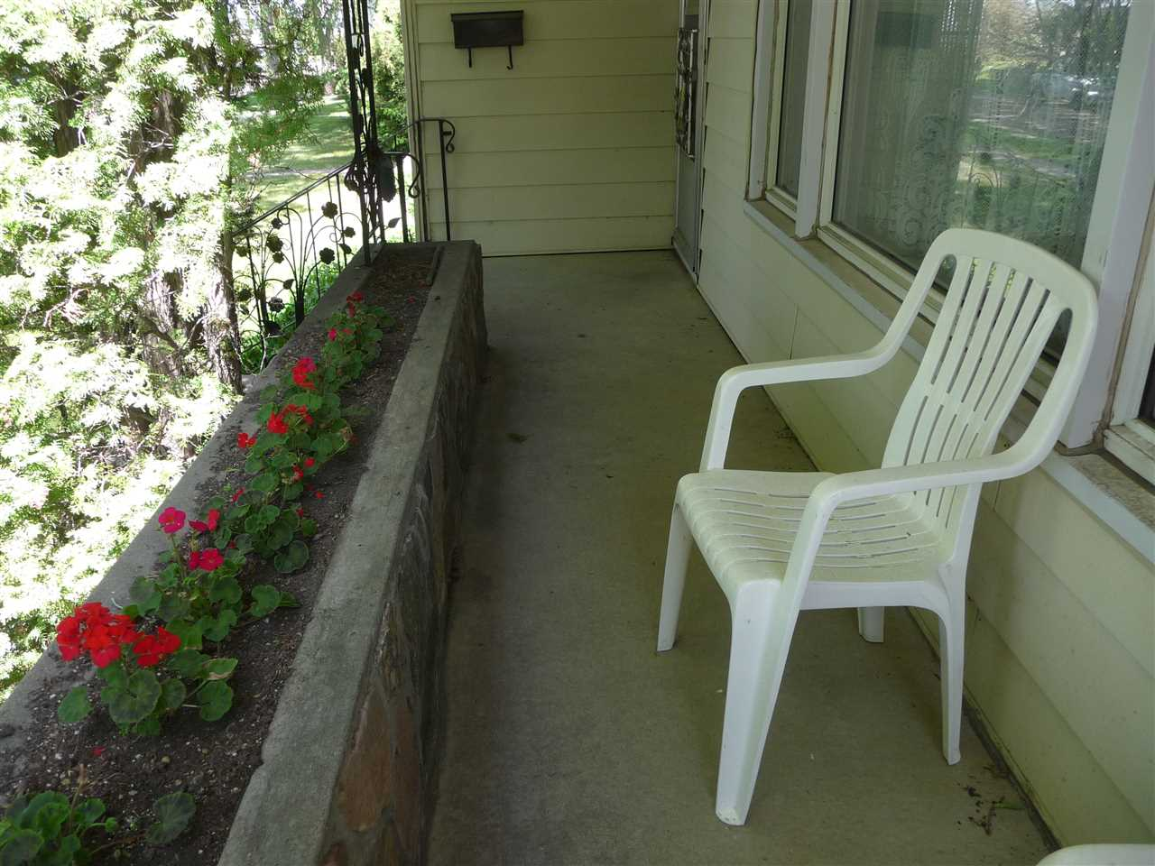 Front veranda overlooks mature landscaping
