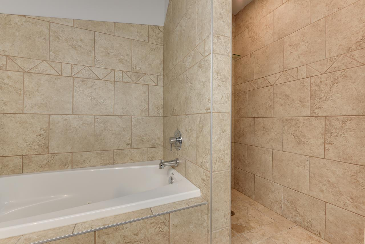 Soaker tub and walk-in tiled shower.