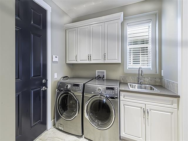 Main floor laundry room with cabinets, sink and built-in lockers.