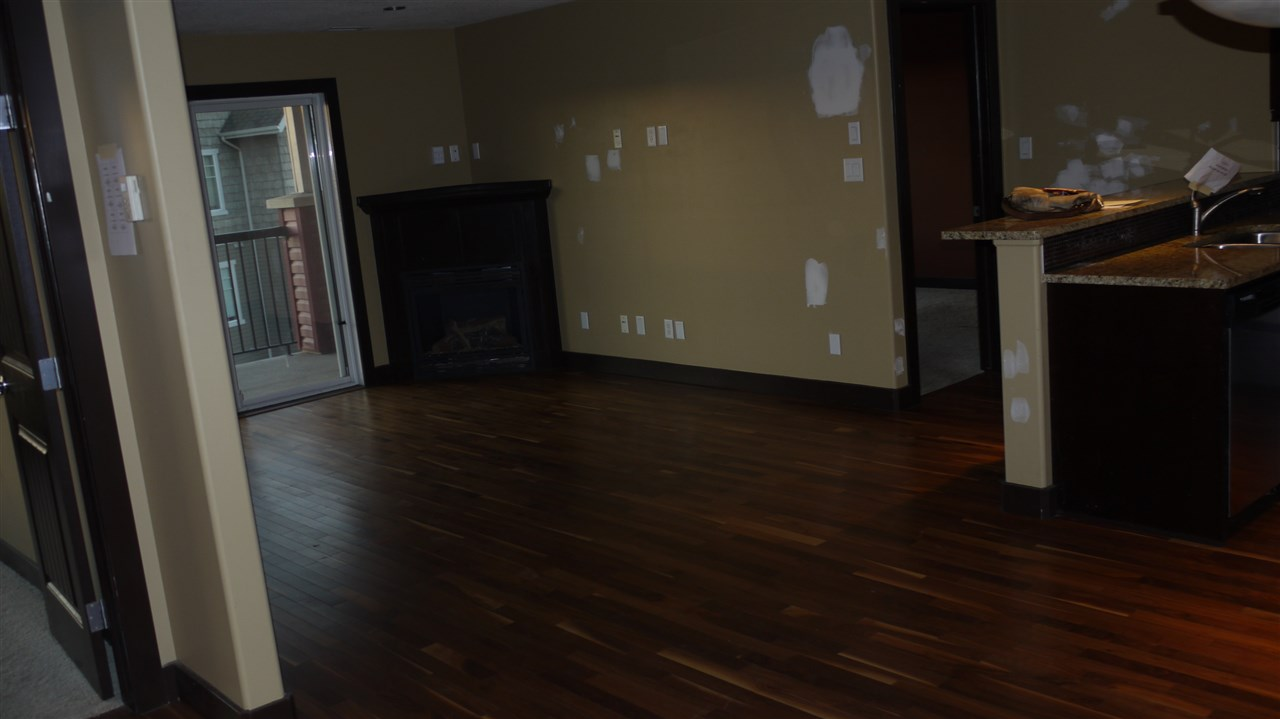 open concept layout with two bedrooms on the opposite side of the unit. hardwood floor in the living room