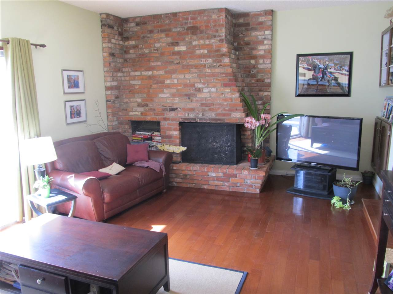 Sunken family room with brick facing, wood burning fireplace and patio doors to back yard deck