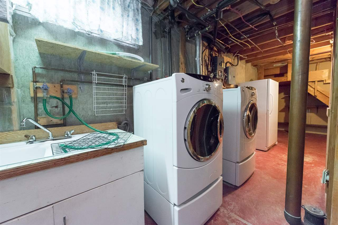 Bright laundry room with window, sink, pedestal washer & dryer and upright deep freezer...
