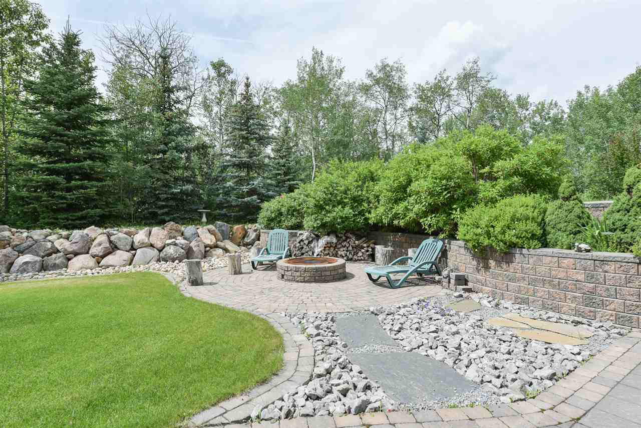 Completely treed and landscaped private setting in Aspen Wood Estates has spiral staircase to upper deck and fire pit area