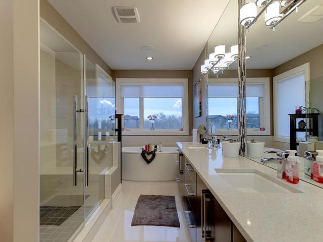 Luxurious ensuite with oversized custom shower, free standing soaker tub and His & Her sinks.
