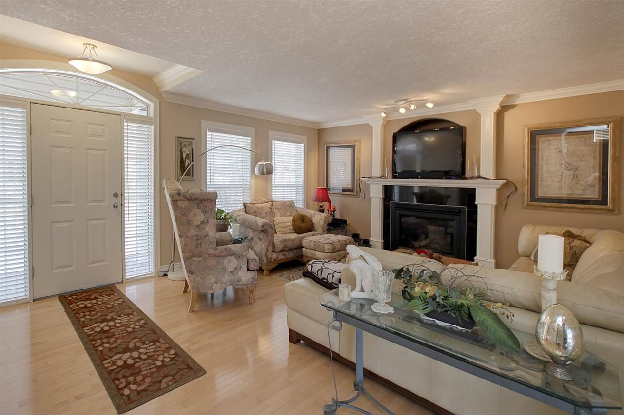 This lovely space boasts a gas fireplace with custom surround, hardwood floors, crown moldings & knockdown ceiling texture (found throughout the home).