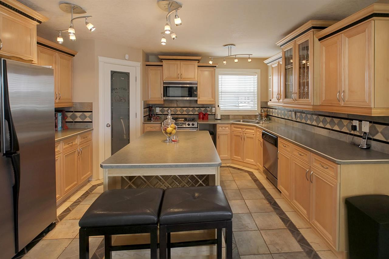 The kitchen boasts loads of custom maple cabinets with fluted borders & moldings, huge island, custom tiled tops & backsplash, pantry & high-end stainless steel appliances.
