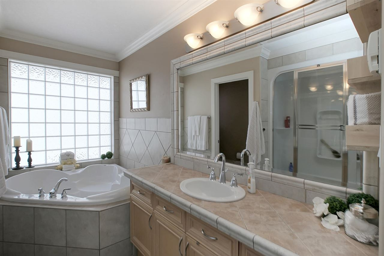 The lavish ensuite offers a huge oval shaped jetted tub, a second tub with steam shower, designer tile tops & heated floors & crown molding.