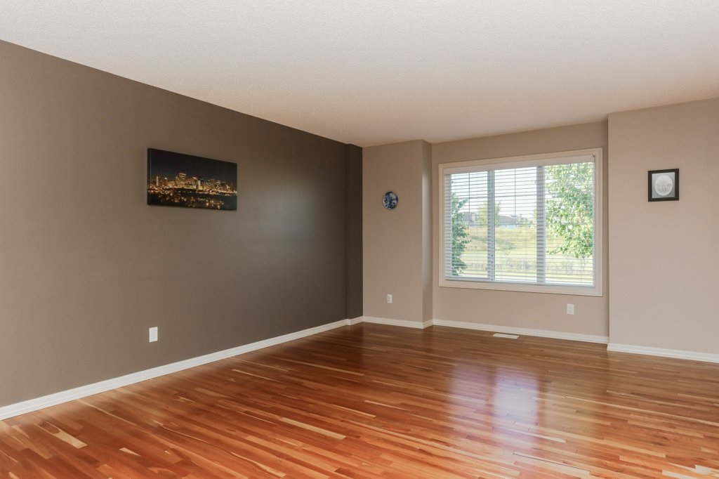 A spacious living room with beautiful hardwood. Perfect for entertaining and relaxing at the end of a long day.