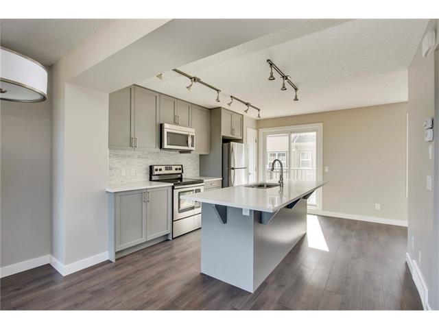 Beautiful open kitchen complete with quartz countertops and laminate flooring.