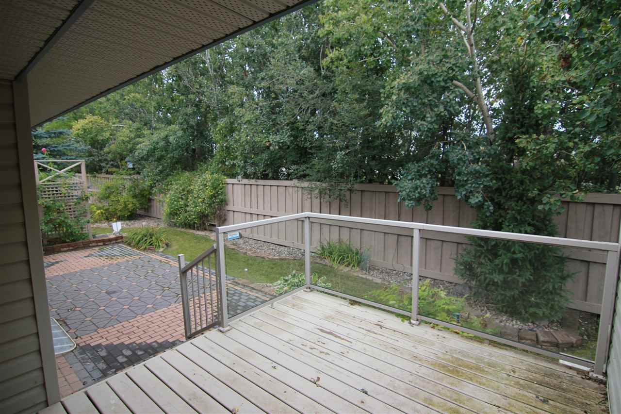 The deck is partially covered and has stairs down to the stone patio for additional entertaining space.