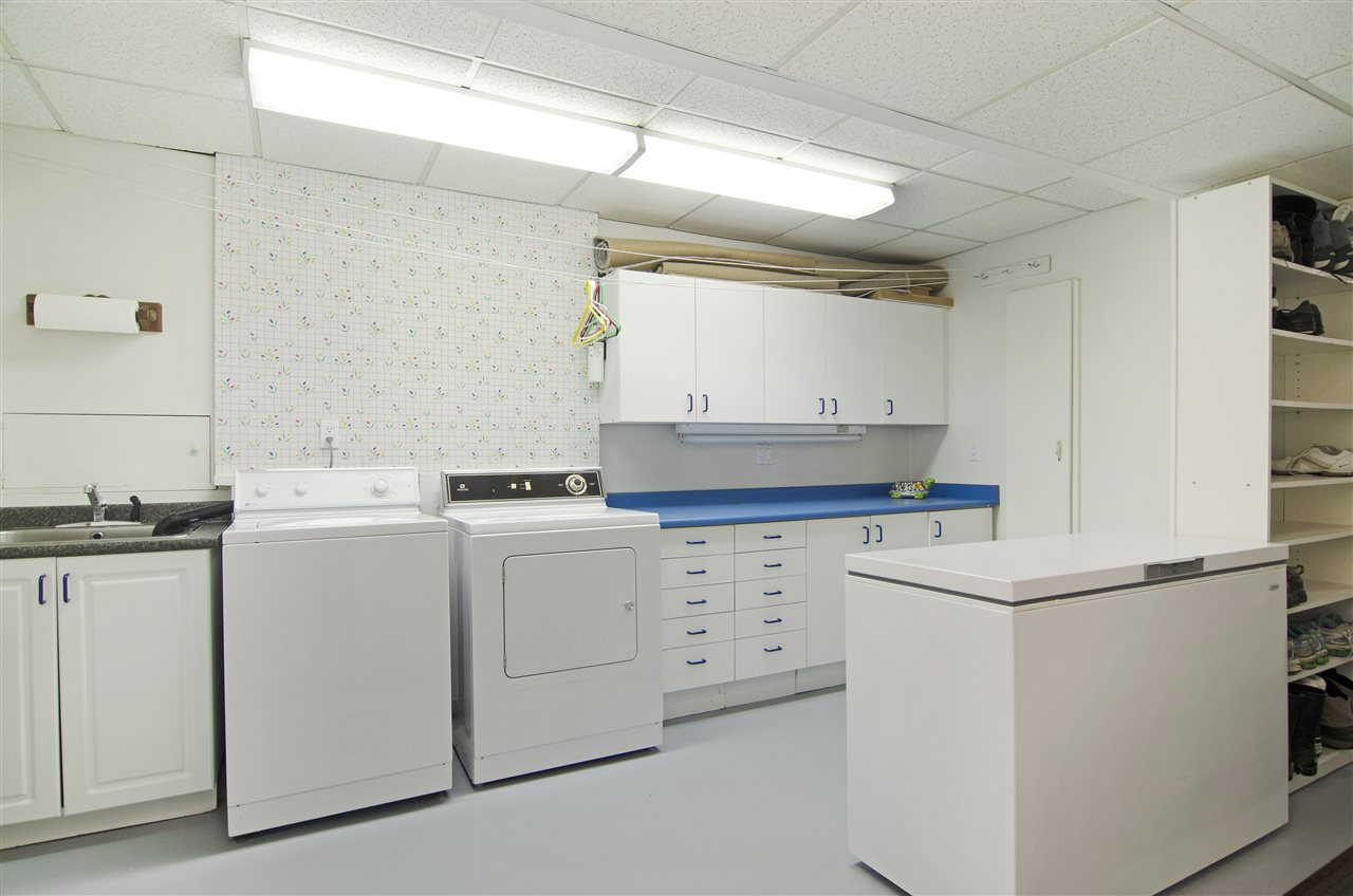 Large laundry room with ample storage cupboards and shelving