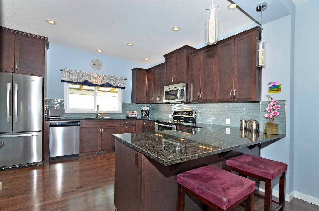 The large kitchen offers granite, stainless steel, pot lights, under cabinet lighting and lots of space 91 Drake Landing Loop, Okotoks Real Estate Listing