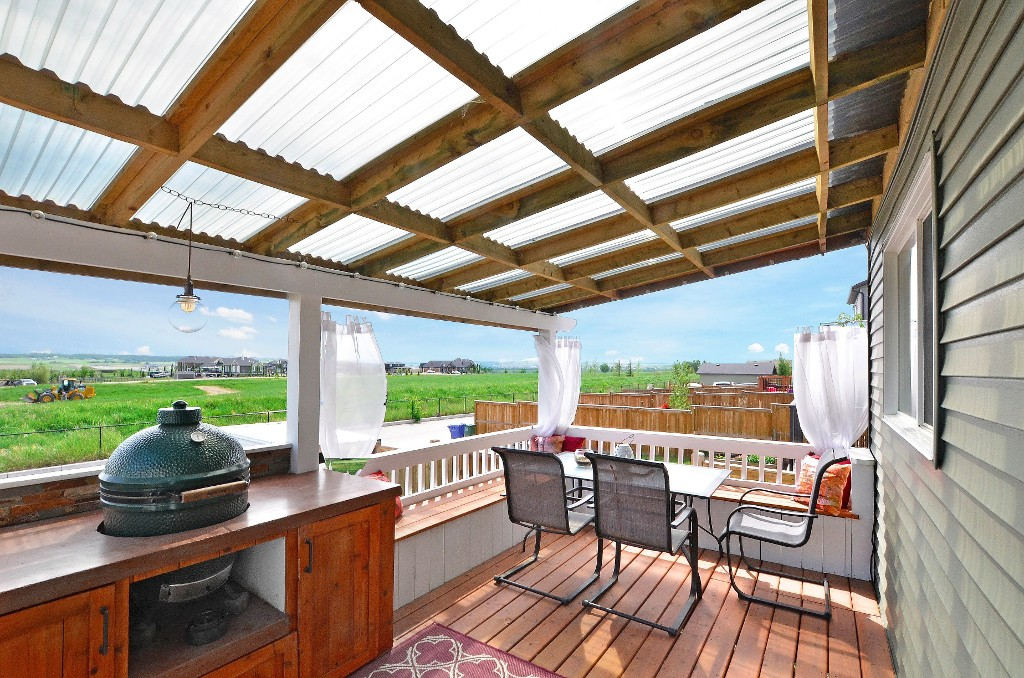 Can you say AMAZING? Enjoy the stunning mountain views from this covered deck while you grill your dinner in the built-in Big Green Egg Cooker. 91 Drake Landing Loop, Okotoks Real Estate Listing