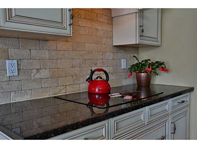 Wonderful feature with the tile back splash and sleek stove top