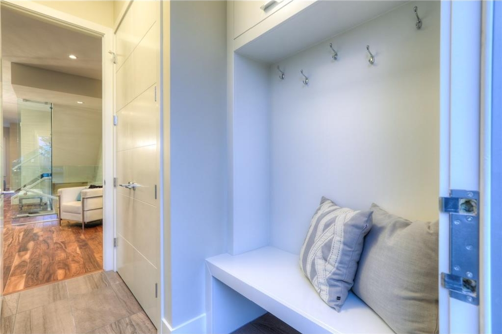 Enclosed rear mudroom with hooks and storage space.
