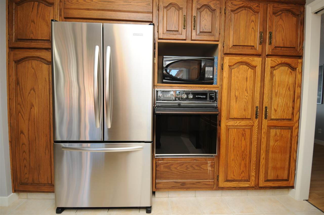 More cabinet space and a large newer stainless steel refrigerator.