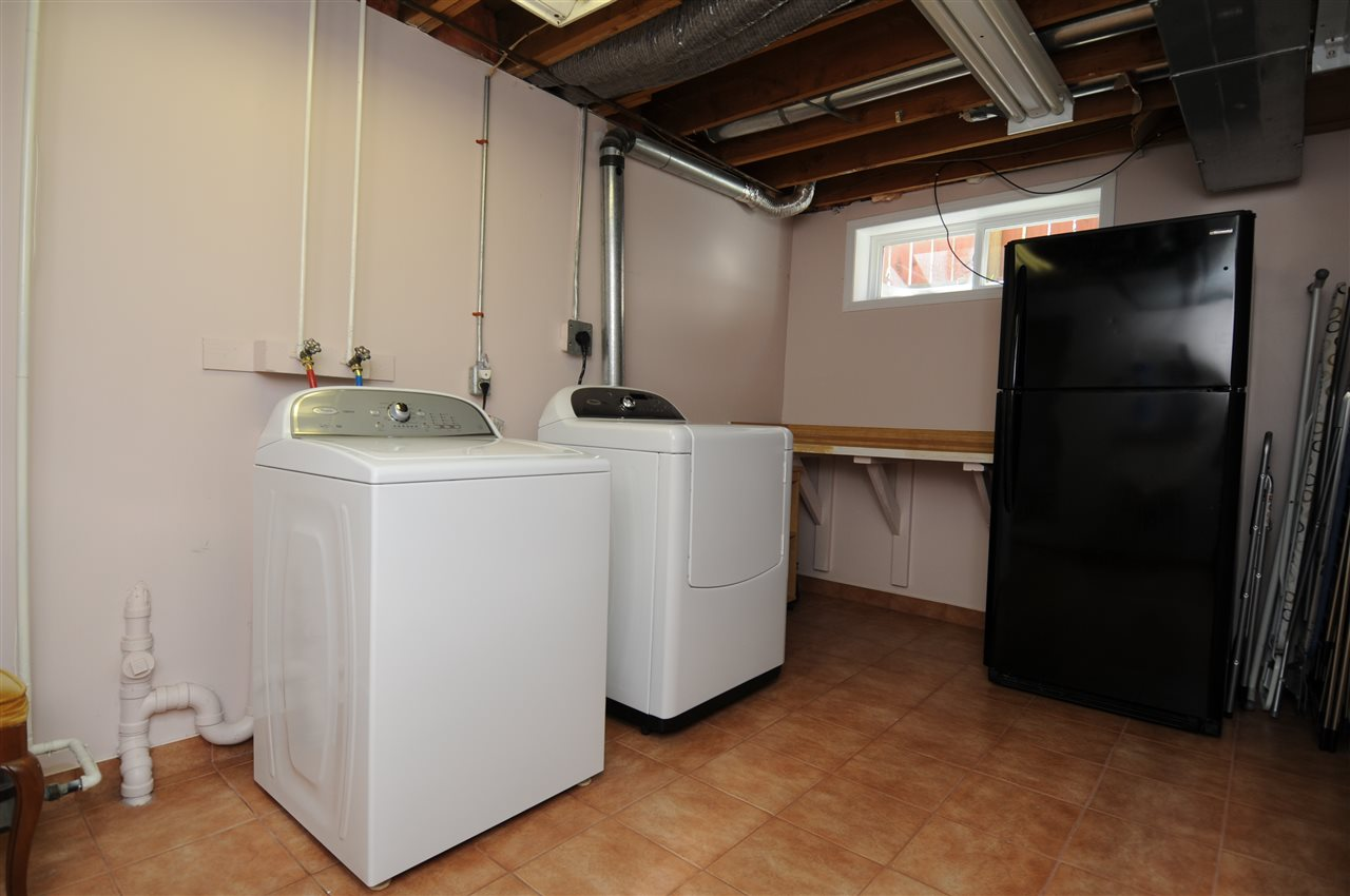 This very clean room has lots of room for storage. At the far end of this big laundry room is a shower. There is also a salon sink that was probably used by a previous owner for a home based business.