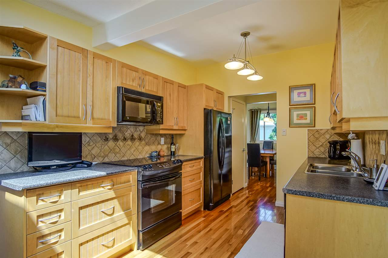 Beautiful Kitchen with Updated Cabinetry, Black Appliances and Hardwood Flooring