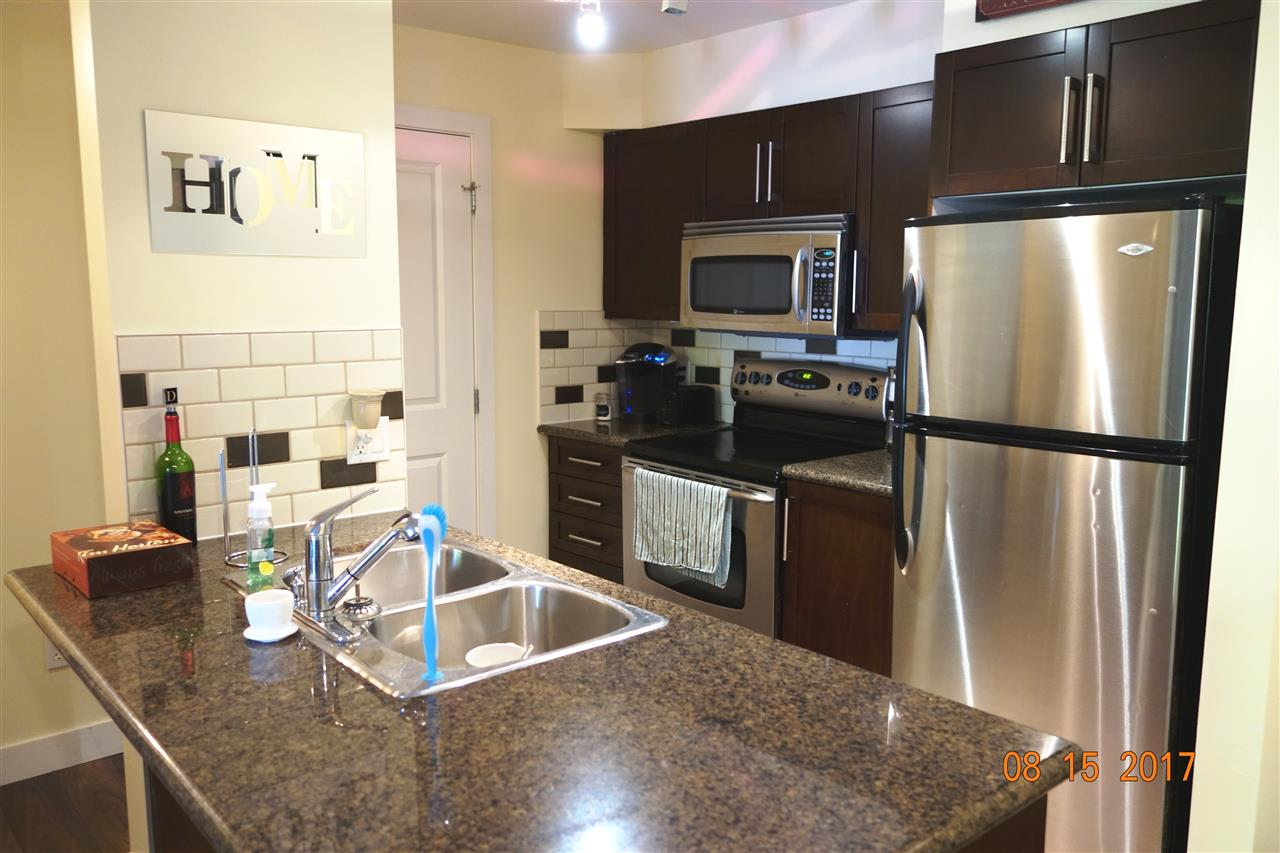 Gourmet kitchen features stainless steel appliances, granite countertops, and tiled backsplash.
