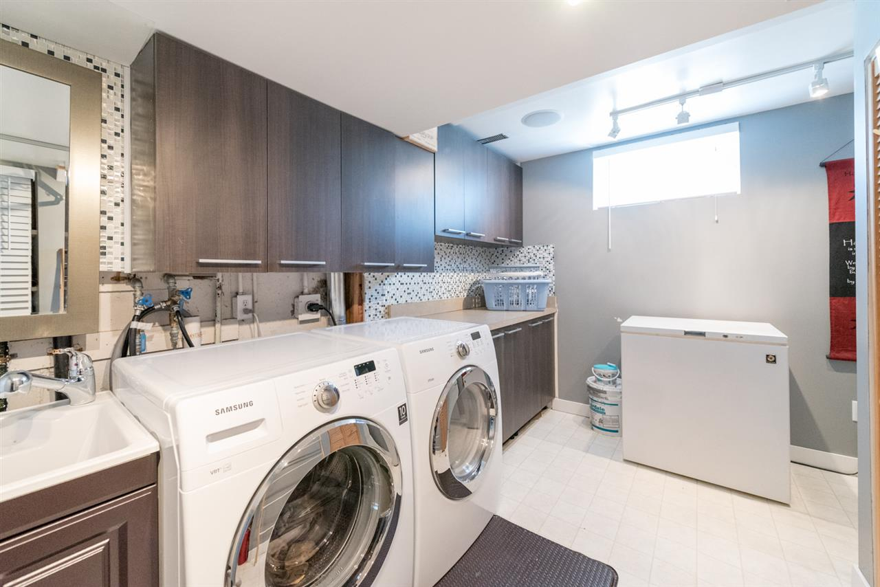 Laundry room features sink, plenty of cabinetry/storage and window...