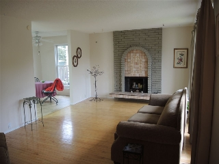 Living room with hardwood floor and a woodburning fireplace