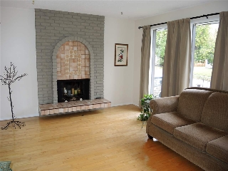 Living room with a wood burning fireplace and brick surround - large windows providing great views!