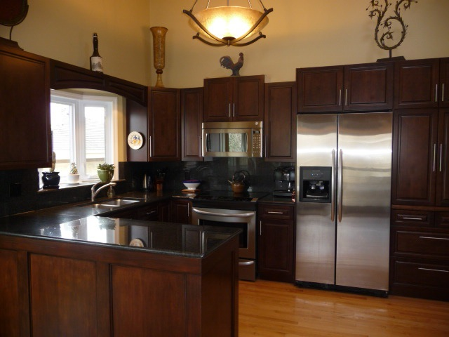 Rich dark wood cabinets, granite counters, garden window above sink - & open to the living area.
