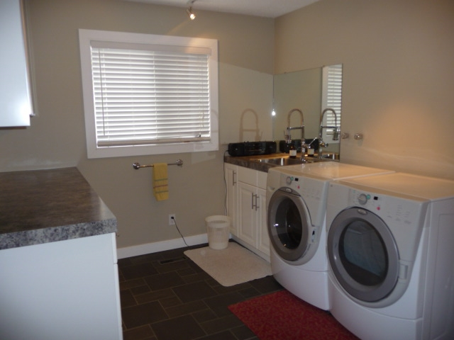 A large main floor laundry room with spacious counter, closet, sink & room to organise.
