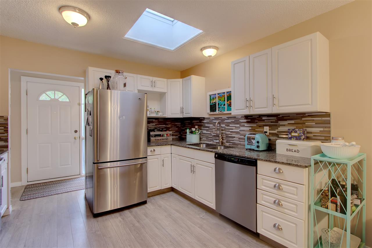 What a great kitchen to enjoy. The clean white cabinets offer plenty of storage, the stainless steel appliances add a modern touch. The granite counter tops add a touch of class and the new backsplash was the perfect addition. There's also a sky light.