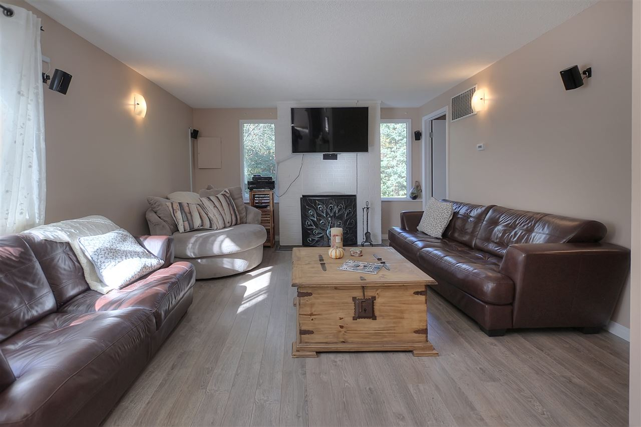 The living room is at the back of the main floor. That offers not only extra privacy, but windows that look out onto your own natural sanctuary. The wood burning fireplace adds even more charm in winter. The vinyl plank flooring centers the area.