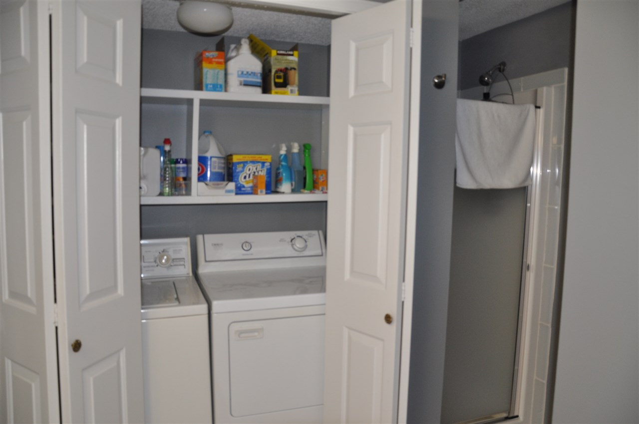 showing laundry and shower stall in the lower bathroom