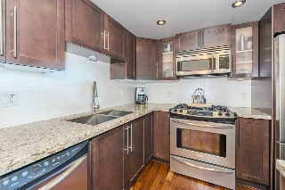 Kitchen with granite counters and tiled back splash.