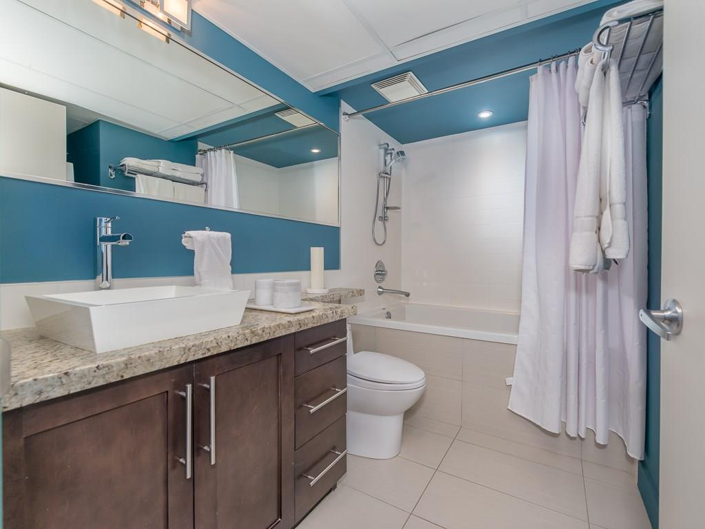 Four-piece bathroom with granite counters, tile floor and deep soaker tub.