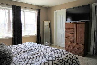 Spacious master bedroom with large windows allowing for plenty of natural light to flow.  The large walk in closet with a window will be a favorite